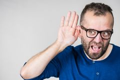 Man eavesdropping with hand close to ear. Man in eyeglasses having troubles with hearing, being deaf. Guy gesturing eavesdropping with hand close to ear stock image