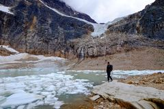 Man ecologist in nature by lake with icebergs. Stock Photo