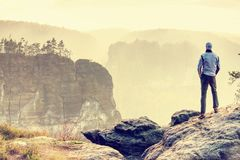 Man on edge of cliff high above misty valley. Travel hiking and Lifestyle. Man walking on the edge of a cliff high above misty valley. Travel hiking and stock photos