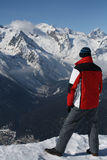 The man at the edge of the cliff in the snowy mountains. Of the Alps on a small village Royalty Free Stock Photo