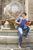 Man on edge of fountain with book, smiling Royalty Free Stock Photos