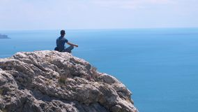 Man on the edge meditating, sits on top of the rock against a background of sea and the blue sky Stock Photography