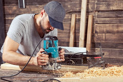 Man edges wooden with a milling machine royalty free stock image