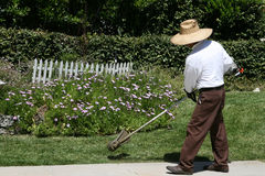 Man edging grass landscaping. Man wearing a hat trimming the edge of a landscaped lawn with a weedeater Royalty Free Stock Photos