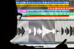 Man Editing Digital Audio on a Computer. Silhouette of a man using a Digital Audio Workstation to edit sound Stock Image