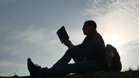 Man education concept. male silhouette reading a book at sunset sitting on lifestyle the lawn sunlight stock footage