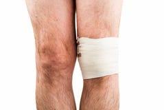 Man with elastic bandage on knee Stock Photos