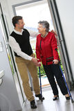 Man and elderly woman at the front door Royalty Free Stock Photography