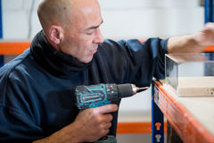 Man with Electric Drill Inspecting His Work. A man with a cordless electric drill examining his work Royalty Free Stock Photography