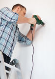 Man with electric drill making hole in wall Stock Photography