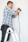 Man with electric drill making hole in wall Royalty Free Stock Images