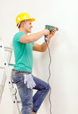 Man with electric drill making hole in wall Royalty Free Stock Photography