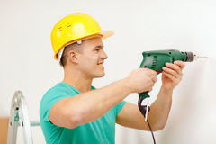 Man with electric drill making hole in wall Stock Images