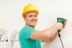 Man with electric drill making hole in wall Stock Image