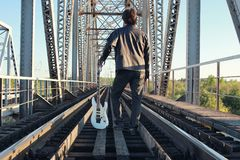 Man with an electric guitar in the industrial landscape outdoors Royalty Free Stock Photos