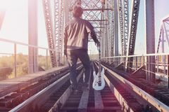 A man with an electric guitar on the railway. A musician in a le. Ather jacket with a guitar on the street in the industrial zone. Guitarist on the bridge.r royalty free stock photography