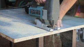 Man with electric jigsaw. Cutting board stock footage