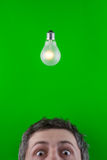 Man and electric light bulb. A view of the top half of a man's head underneath a traditional incandescent light bulb.  Bright green background.  Theme:  bright Stock Photos