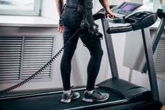 Man in electric muscle stimulation suit for ems training running on treadmill. Fit Man in black electric muscle stimulation suit for ems training running on Royalty Free Stock Photography