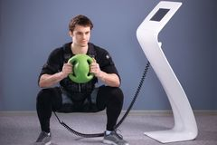 Man in electric muscular suit to stimulate with training medecine ball. Fit Man in electric muscular suit to stimulate with training medecine ball Stock Photo