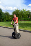 Man on an electric scooter-Segway. A man on an electric scooter-Segway Royalty Free Stock Photos
