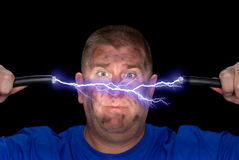 Man and electrical arc. An electrician plays with some live wires, causing an arc of electricity and charring the man's face Stock Image