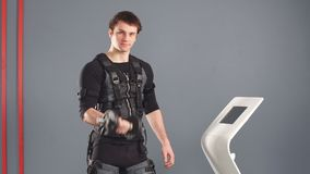 Man in Electrical Muscular Stimulation suit standing with dumbbells near ems tablet and push on screen. Man in Electrical Muscular Stimulation suit standing stock video footage