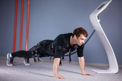 Man in Electrical Muscular Stimulation suits doing plank exercise. EMS stock photo