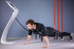 Man in Electrical Muscular Stimulation suits doing plank exercise. EMS stock photos