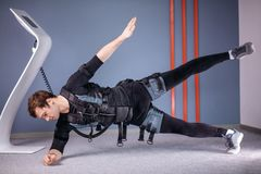 Man in Electrical Muscular Stimulation suits doing side plank exercise. EMS. Fit man in Electrical Muscular Stimulation suits doing side plank exercise. EMS Stock Image