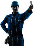 Man electrician holding light bulb silhouette Royalty Free Stock Images