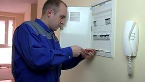 Man electrician work on circuit breaker in room. Profession. 4K stock video