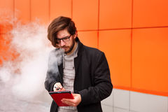 Man with electronic cigarette and Tablet PC. Royalty Free Stock Photography