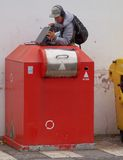 Man on electronic waste container. The man pulls out the discarded device from a red container for electronic waste Stock Photo