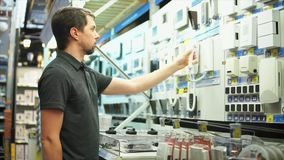 Man in the electronics shop is choosing intercom security system and alerts stock footage