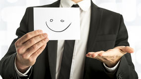 Man in elegant business suit holding up a white card with smiley Stock Photo