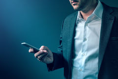Man in elegant business suit looking at mobile phone screen Royalty Free Stock Images