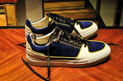Man elegant and casual sport shoes. With white and blue leather yellow line and black lace-ups . they look interesting especially on that brown parquet Royalty Free Stock Image