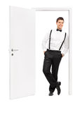 Man in elegant clothes posing by an opened door Royalty Free Stock Images