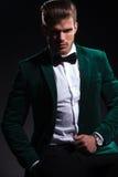 Man in elegant green velvet suit is sitting on a chair. Young fashion man in elegant green velvet suit is sitting on a chair and is looking at the camera on Stock Photos