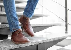 Man in in elegant shoes walking down stairs. Indoors stock images