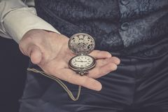 Man holds pocket watch in his hand stock image