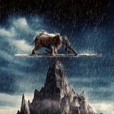 Man and an elephant pushing eachother. And balacing on top of a peak in the rain royalty free stock image