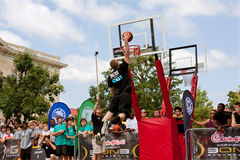 Man Elevates Above Rim In Outdoor Street Slam Dunk Contest Royalty Free Stock Image