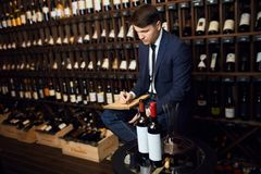 Man in ellegant trendy suit writing down information about wine product royalty free stock photo