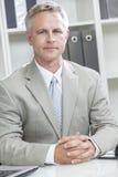 Man eller affärsman som i regeringsställning sitter på skrivbordet Fotografering för Bildbyråer