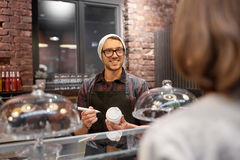 Man eller bartender med den kaffekoppen och kunden på kafét Arkivbild