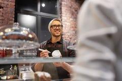 Man eller bartender med den kaffekoppen och kunden på kafét Arkivfoto