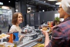 Man eller bartender med kakaportionkunden på kafét Arkivbild