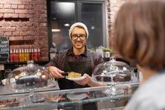 Man eller bartender med kakaportionkunden på kafét Royaltyfri Bild